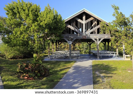 Hollywood, FL, USA - December 20, 2014: Weathered wooden pavilion covered with open sides and picnic tables in John U Lloyd Beach State Park near Port Everglades.