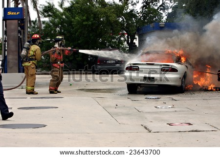 HOLLYWOOD, FLORIDA - SEPTEMBER 3: Capt Austin [left] and Driver Fresco fighting a fire on a car at a gas station September 3, 2007 in Hollywood, Florida. - stock photo
