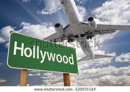 Hollywood Green Road Sign and Airplane Above with Dramatic Blue Sky and Clouds. - stock photo