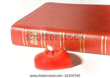 Holy Bible and a red heart-shaped candle - stock photo