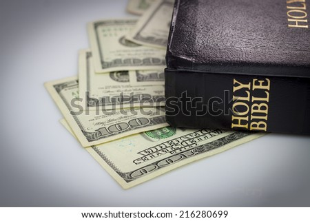 Holy Bible and money. Hundred dollars - stock photo