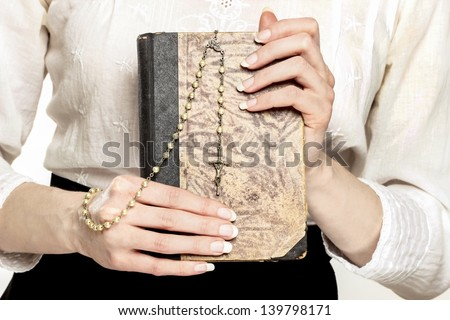 Holy Bible and white rosary in beautiful hands - stock photo