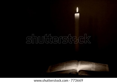 Holy Bible lit by candle light in a vintage style. - stock photo