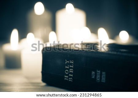 Holy Bible on candle background - stock photo