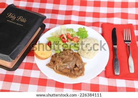 Holy Bible on red plaid tablecloth  -- Sunday Potluck dinner of Salisbury steak in brown gravy with onions and mushrooms on white plate with mashed potatoes and tossed salad and cornbread muffin. - stock photo