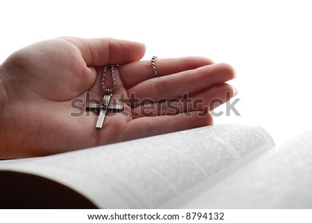 holy bible open with a cross on a hand - stock photo