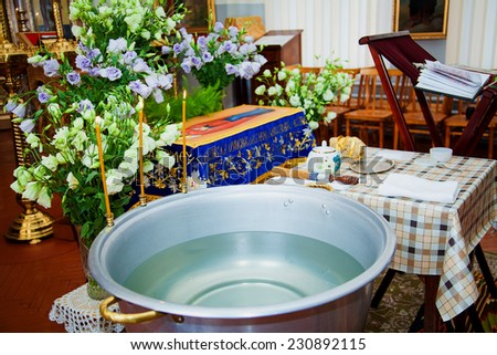 Holy Bible, Orthodox cross and Bowl prepared for christening ceremony in russian church - stock photo