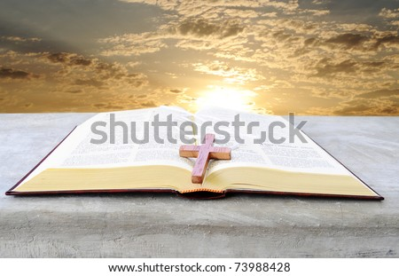 Holy bible over a pulpit with a bright sunrise as background - stock photo