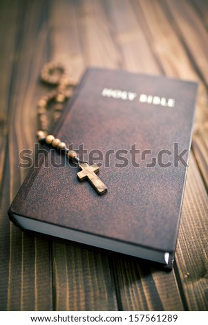 holy bible with rosary beads on wooden background - stock photo