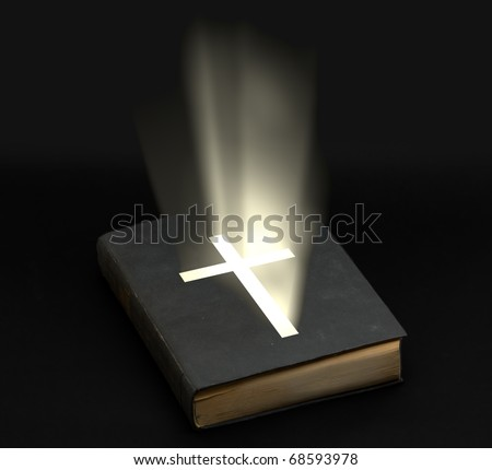 Holy bible with shining cross over black background - stock photo
