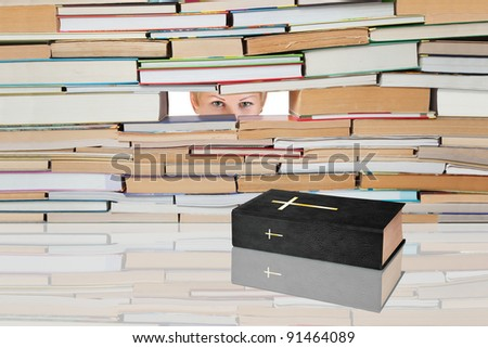 Holy Book against the backdrop of numerous books and looking women. - stock photo