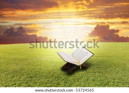 Holy book Koran, opened on the meadow with light shining from inside - stock photo
