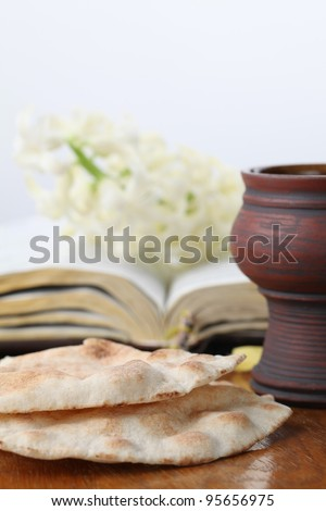 Holy communion. Chalice with red wine, pita bread, Holy Bible and white hyacinth - stock photo