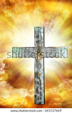 holy cross against a bright sunny sky with sunshine light and clouds - stock photo