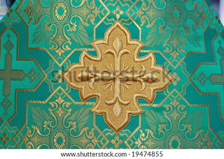 Holy Cross on green solemn slavic orthodox priest's mantle - stock photo