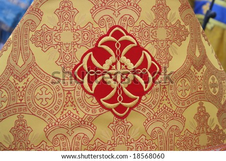 Holy Cross on slavic orthodox priest's yellow mantle - stock photo