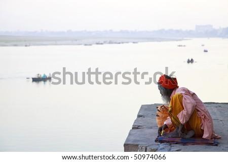 Holy indian Sadhu at the ghats in Varanasi,India. - stock photo