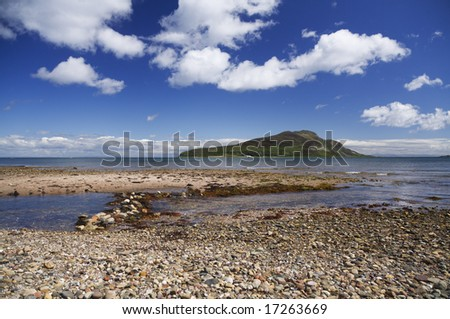 Holy Isle just off an Arran Beach in Scotland - stock photo