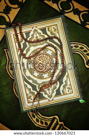 Holy Quran Book With Rosary on Prayer Carpet - stock photo