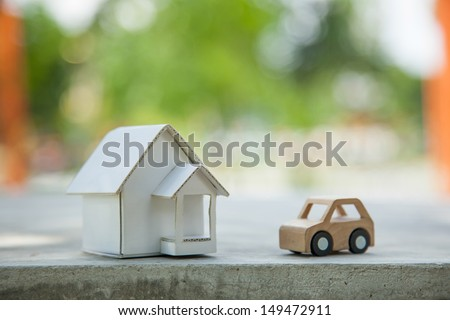 Home and car artificial on the concrete. - stock photo