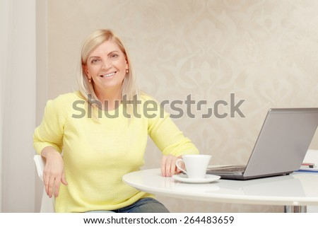 Home atmosphere. Cheerful mature woman smiles at a camera sitting by the table with laptop and cup of coffee on it - stock photo