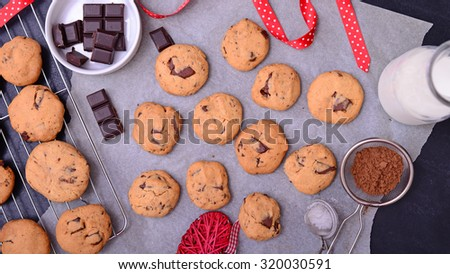 Home baked chocolate cookies on baking paper with ingredients, close-up - stock photo