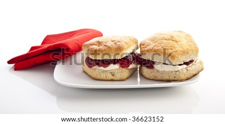 Home-baked scones with strawberry jam and clotted cream, often served with a cup of tea. Known as a cream tea. - stock photo