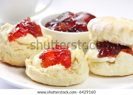 Home-baked scones with strawberry jam and clotted cream, served with a cup of tea.  Known as a Devonshire tea. Focus on front scone. - stock photo