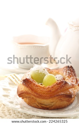 home bakery, autumn grape on Danish pastry with tea on background,