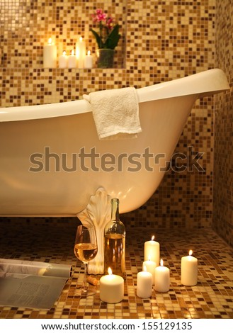 Home bathroom interior with bubble bath, candles, magazine and white whine. Relax concept - stock photo