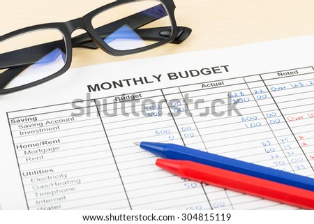Home budget planning sheet with pen and glasses - stock photo
