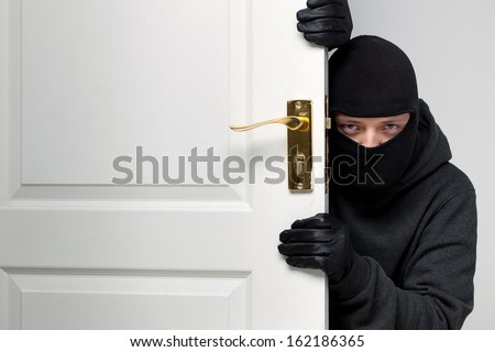 Home burglary concept with a burglar sneaking in a open house door - stock photo