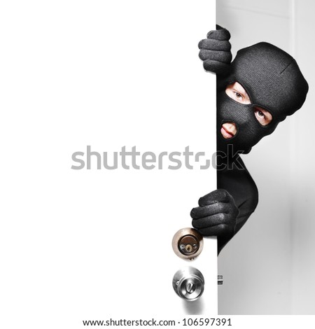 Home burglary concept with a burglar sneaking in a open house door during a break and enter past security locks and alarms, white background with copyspace - stock photo