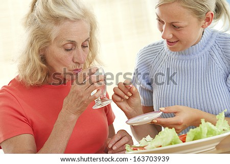 Home care nurse helping elderly lady to take her daily medicine.  - stock photo