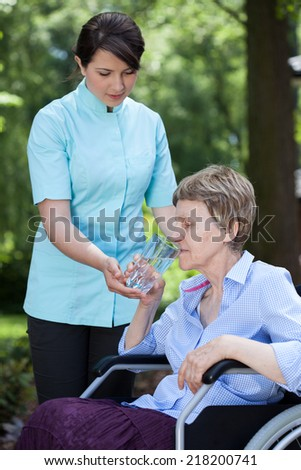 Home caregiver giving glass of water to senior woman - stock photo