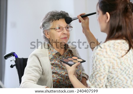 Home carer helping elderly woman to put makeup on - stock photo