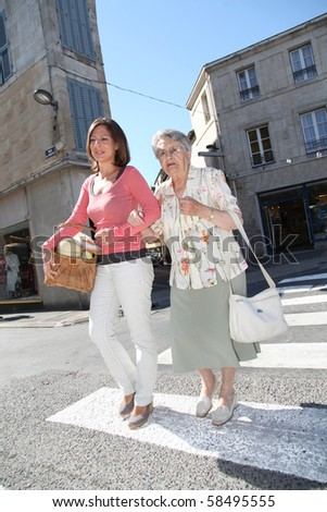Home carer with elderly person in town - stock photo