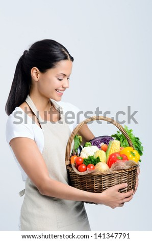 Home chef holds a basket of freshly picked vegetables from her home garden - stock photo
