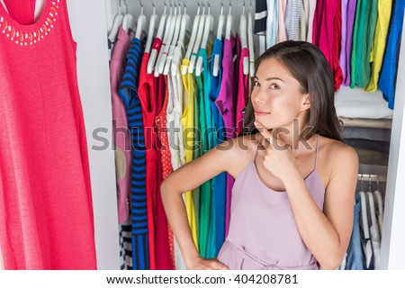 Home closet or store clothing rack changing room. Woman choosing her fashion outfit. Shopping girl thinking what to wear in front of many choices of dresses and clothes in organized clean walk-in. - stock photo