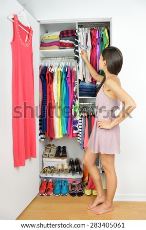 Home closet - woman choosing her fashion clothing. Shopping concept. Woman having many new clothes facing indecision in front of many choices of stylish dresses and skirts in organized clean walk-in. - stock photo