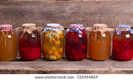 Home compotes on wooden boards. Natural drinks on an old wooden shelf. Canned juices in the cellar. - stock photo