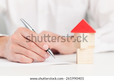 Home. Conceptual image of a man signing a mortgage or insurance contract or the deed of sale when buying a new house or selling his existing one with a small wooden model of a house alongside - stock photo