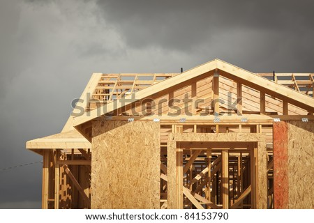 Home Construction Framing with Ominous Grey Clouds Behind. - stock photo