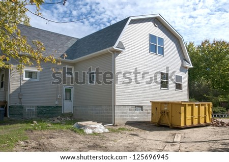 Home construction with gabled roof design and trash receptacle - stock photo