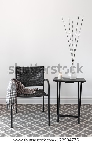 Home decor. Black armchair and little table decorated with decorations. - stock photo