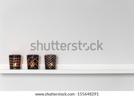 Home decor, candle lights on a white shelf. - stock photo