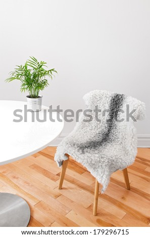 Home decor. Chair covered with sheepskin, and green plant on a white table. - stock photo