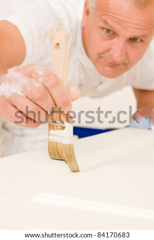 Home decorating mature man painting white door with paint brush