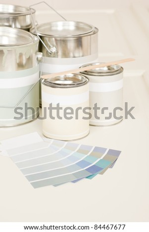 Home decorating paint can and color swatches on white desk - stock photo