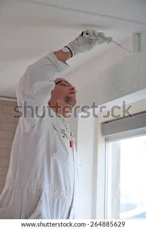 Home decorator painting a wall white with a roller